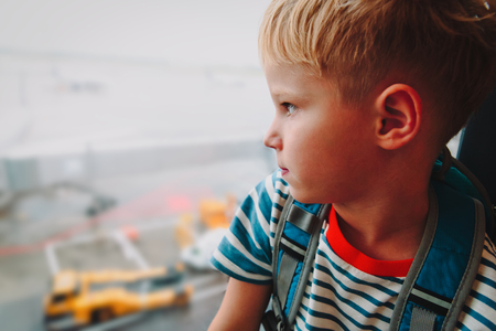 little boy waiting in airport looking at planes, family travel Фото со стока