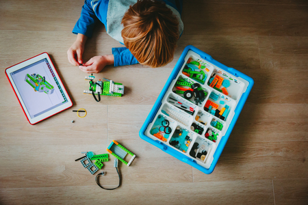 little boy building robot and programming it with touch pad Reklamní fotografie