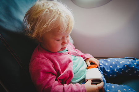 flight safety - little girl fasten seat belt in plane 版權商用圖片