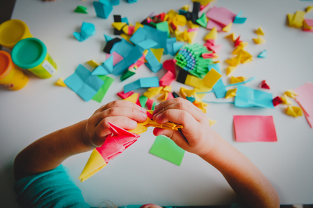 little girl making origami crafts with paper 版權商用圖片