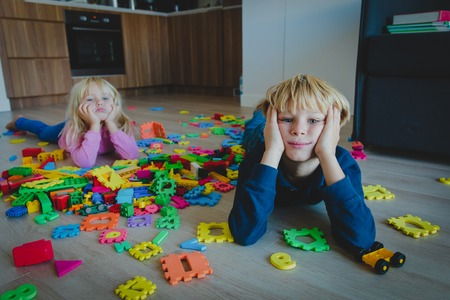 little boy and girl tired stressed exhausted with toys scattered indoors Foto de archivo