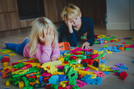 little boy and girl tired stressed exhausted with toys scattered indoors 免版税图像