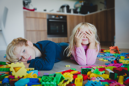 little boy and girl tired stressed exhausted with toys scattered indoors 版權商用圖片