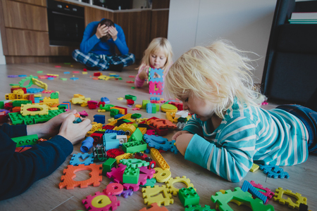 kis play at home with toys scattered all over and tired exhausted father