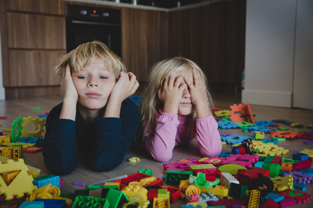 little boy and girl tired stressed exhausted with toys scattered indoors Фото со стока