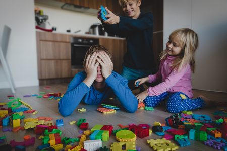 kis play with toys scattered all over and tired exhausted father Stock Photo