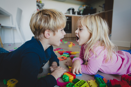 brother and sister shout at home with toys scattered on floor, family problems