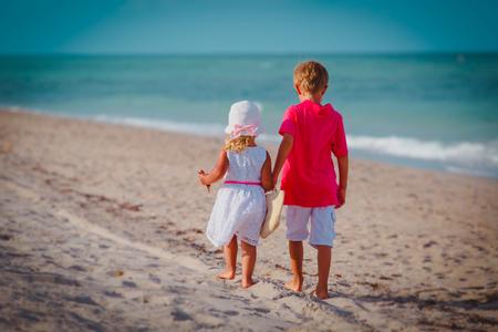 little boy and girl walk on summer beach 写真素材 - 111790365
