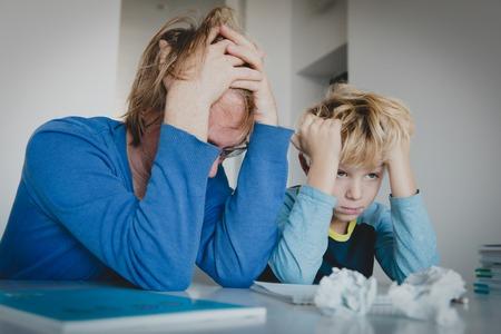 Vater müde, Hausaufgaben mit Sohn zu machen, schwieriges Lernen Standard-Bild