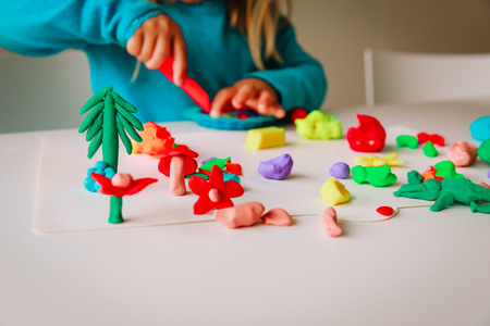 Little girl play with clay molding shapes