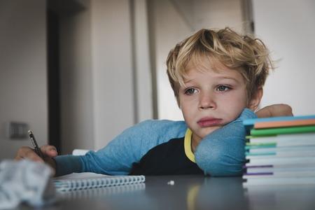 kleiner Junge müde gestresst lesen, Hausaufgaben machen Standard-Bild