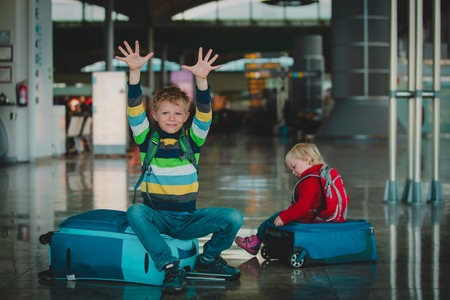 little boy and girl enjoy travel in airport, sitting on suitcases