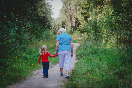senior grandmother with little granddaughter walk in nature 版權商用圖片