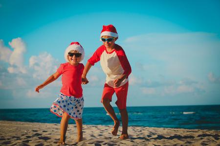 happy kids-little boy and girl- celebrating christmas on beach Stock Photo