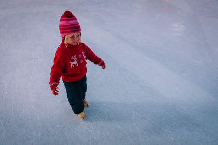 little girl learning to skate on ice in winter