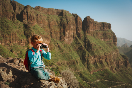 little boy looking through binoculars travel in mountains