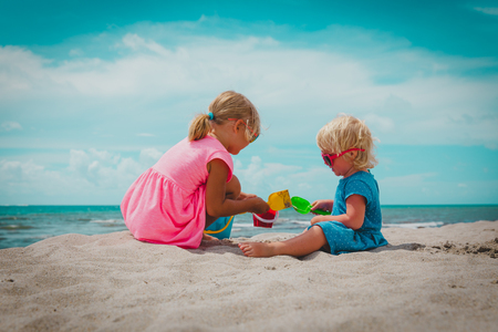 little girls play with sand on summer beach Stockfoto