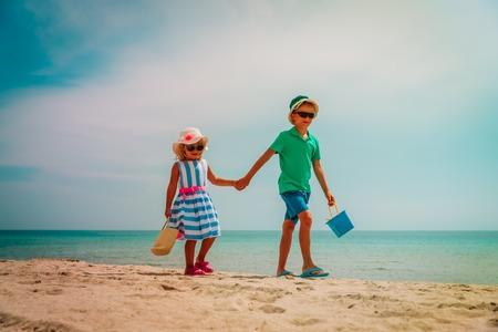 cute boy and girl walk on tropical beach vacation