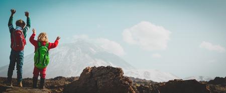 gelukkige kleine jongen en meisje wandelen in de bergen