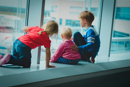 kids looking at planes in airport, family travel