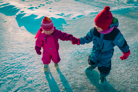 little girls skating together in snow, kids winter sport Banco de Imagens