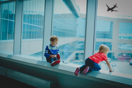 little boy and girl waiting for plane in airport Stock Photo
