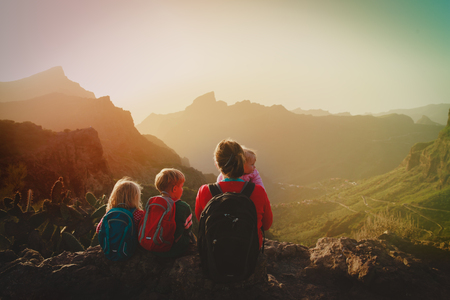 mother with three kids hiking travel in mountains