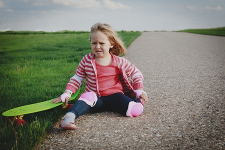crying little girl fall off from skateboard, injury Reklamní fotografie