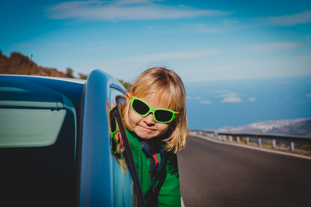 happy little girl enjoy travel by car on road in nature