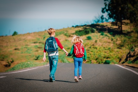 kids go to school - brother and sister with backpacks walking on road