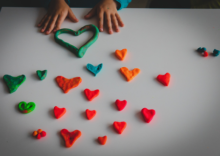 little girl making hearts from clay, valentine day crafts Stock fotó