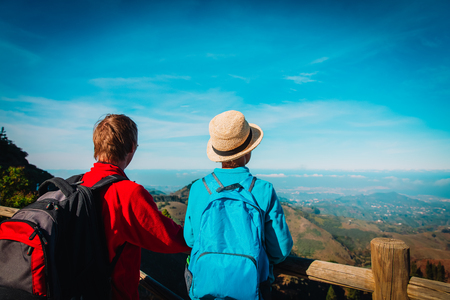 father and son hiking in mountains, looking at scenic view