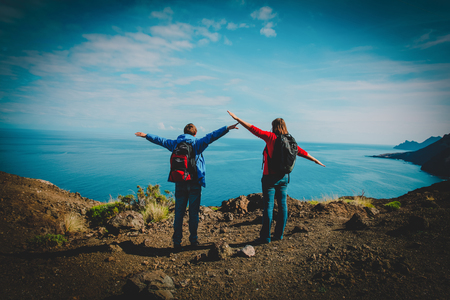 happy young couple hiking in mountains at sea