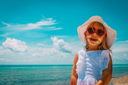 sun protection - happy little girl with suncream at beach Banco de Imagens