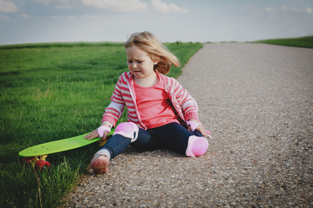crying little girl fall off from skateboard, injury Stock Photo