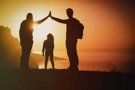 happy family-mom, dad and little daughter-enjoy travel at sunset
