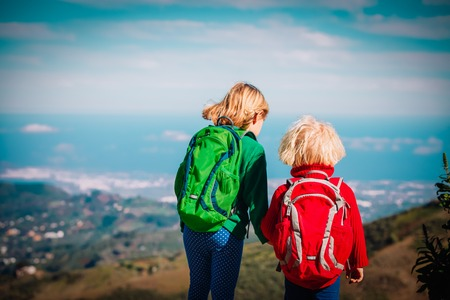 little girls with backpacks travel in nature