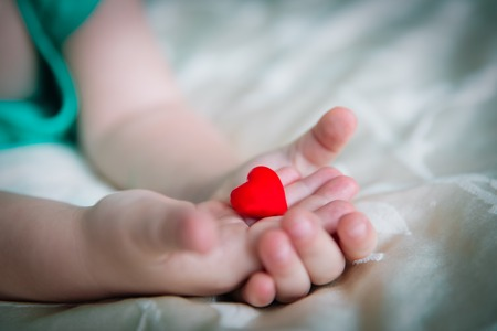 love and family concept. little girl holding heart in hands