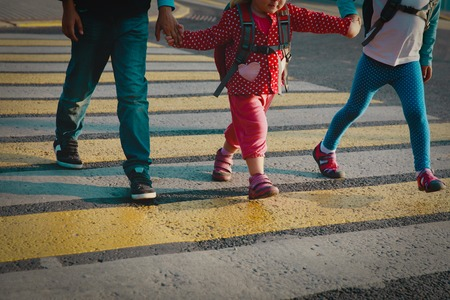 boy and girls holding hands go to school crossing the road