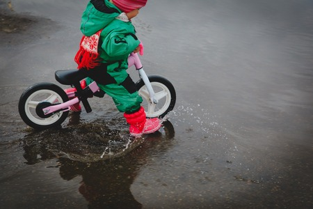 little girl riding bike in spring water puddle