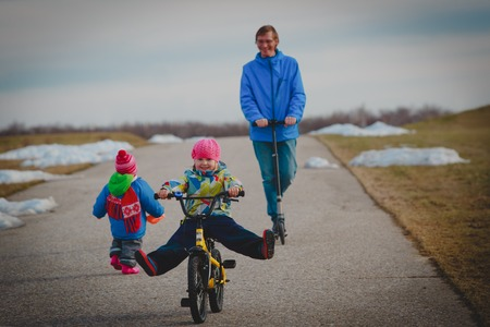 active spor family- father on schooter with kids outside, little girl on bike