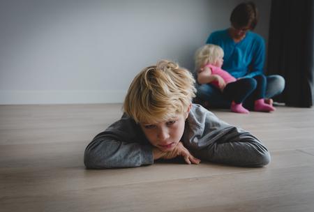Geschwisterrivalität - trauriger Sohn und Vater, die kleine Tochter halten