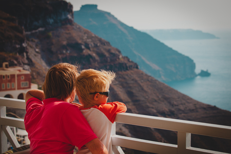 father and little son looking at caldera in Santorini, Greece