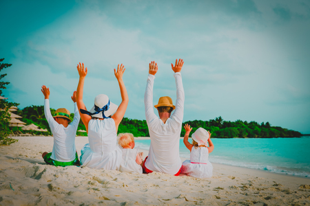 happy family with kids hands up on beach Banco de Imagens