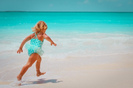 little girl run play with waves on the beach
