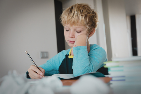 young boy tired stressed of writing, doing homework