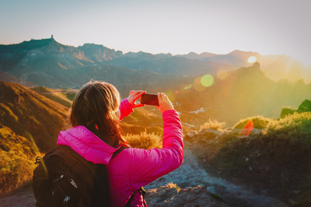 young tourist making mobile phone photo of sunset in mountains