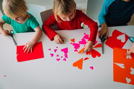 bambini che fanno cuori di carta, si preparano per il giorno di san valentino