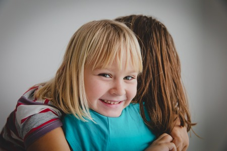 cute smiling little girl hug mother, happy family enjoy being together