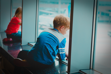 little boy and girl waiting plane in airport